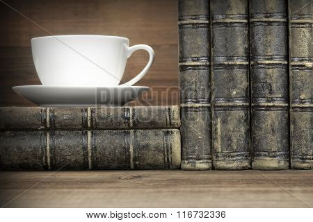 Old Shabby Books And White Cup On The Wood  Background