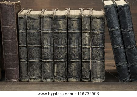 Old Shabby Books In Row On The Rough Wood Table