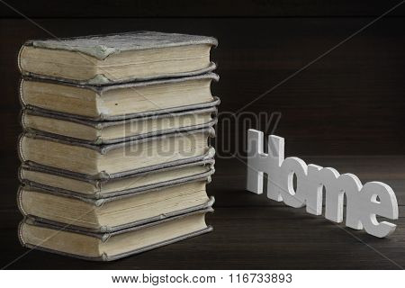Old Books In Stack And Sign Home On Wood Table