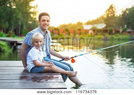 Smiling dad and son fishing outdoors