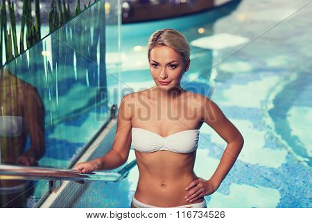 happy woman raising upstairs in swimming pool