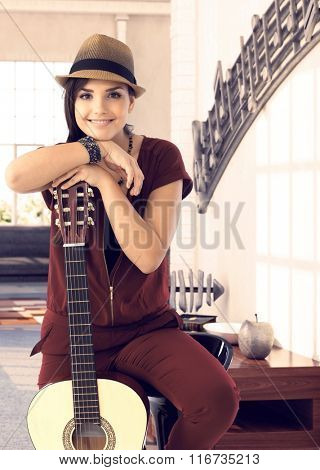 Romantic young woman in hat leaning on guitar, smiling, looking at camera.