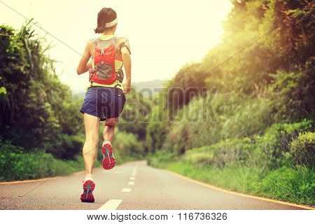 young woman runner  running at forest trail