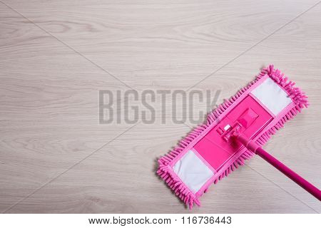 Close Up Of Pink Floor Mop On Wooden Background