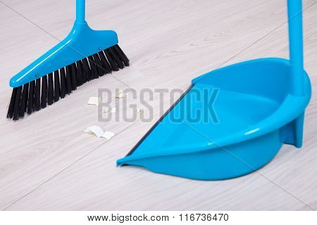 Close Up Of Broom And Dustpan Sweeping Floor