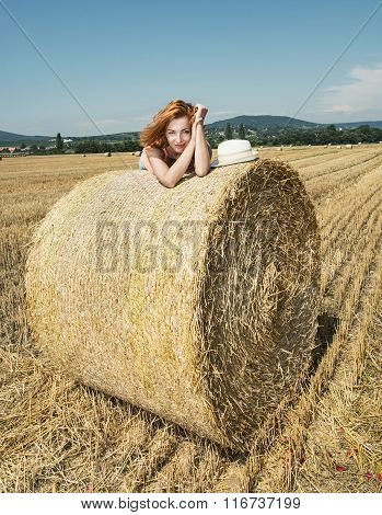 Young Woman Posing With The Stack Of Straw And Enjoying The Sunshine