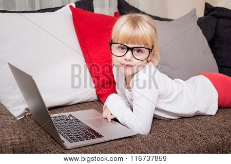 Child with glasses lying on couch with laptop in front of her