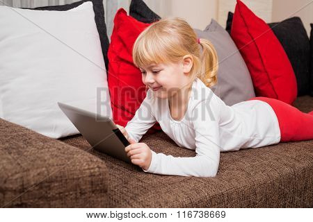 Little girl smiling and using laptop