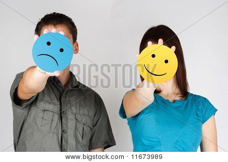 Man And Woman Holding Paper Cards With Sad And Fun Smiles