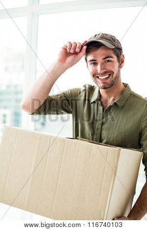Smiling postman holding package in office