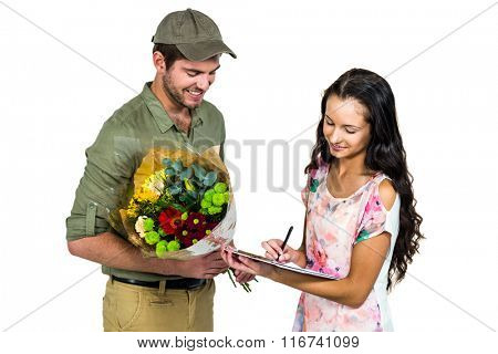 Woman signing for bouquet delivery with smiling postman on white screen