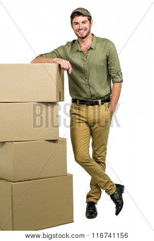 Handsome postman standing by cardboard boxes on white screen