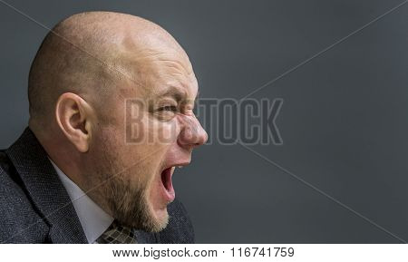 Portrait of an adult man in a business suit on a black background. Side profile portrait of angry man screaming