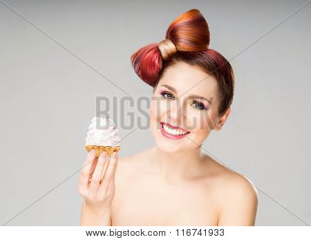 Beautiful woman with a bow haircut holding a cake on grey background.