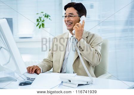 Smiling businessman talking on the telephone in his desk