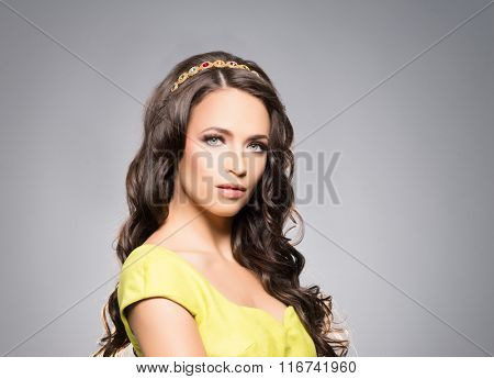 Portrait of young, attractive lady wearing golden coronet over isolated background.