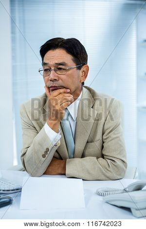 Undecided businessman at his computer in his office