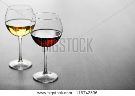 Glasses of wine on wooden background