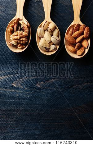 Spoons with walnuts, pistachios and almonds, on grey wooden background