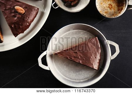 Pieces of frosting chocolate cake on black table