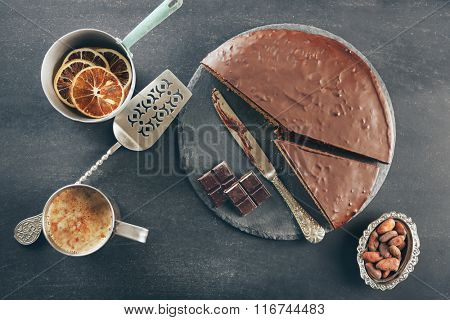 Sliced chocolate frosting cake on black table