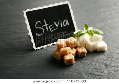 Word STEVIA written on black board and sugar on the table, close up