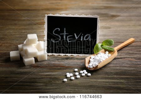 Word STEVIA written on black board and sugar on wooden background