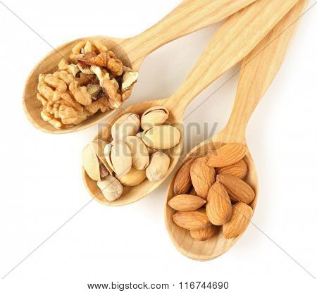Wooden spoons with walnuts, pistachios and almonds, isolated on white