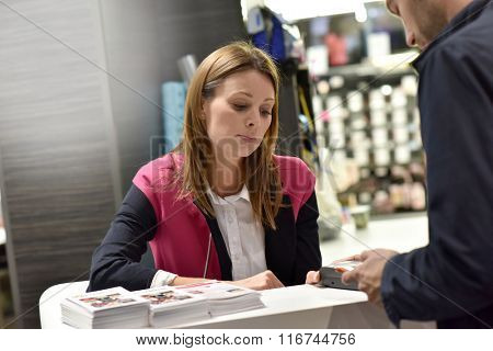 Cashier woman standing at the reception desk of supermarket