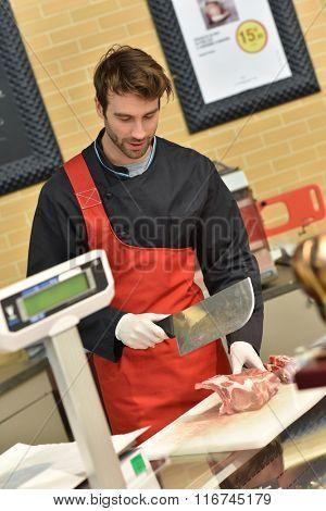 Butcher serving meat in supermarket