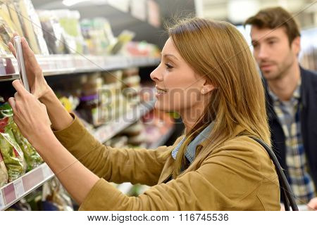 Woman in supermarket scanning barcode with smartphone