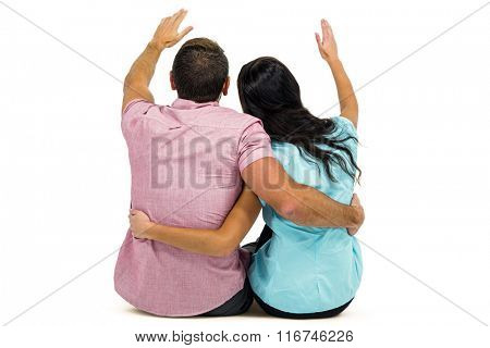 Rear view of couple with arm around while sitting on white screen