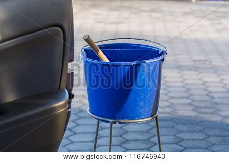 Blue Bucket With Water At A Gas Station