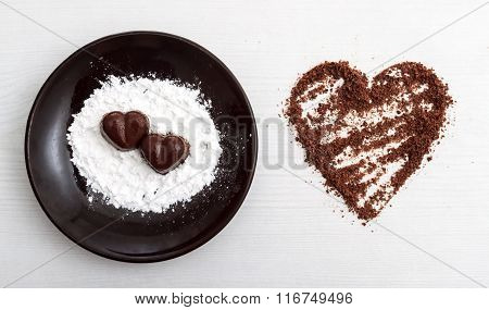 Two Chocolate Heart-shaped Candies On A Brown Plate With Sugar Powder Next To Chocolate Chips