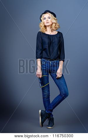 Full length studio portrait of a beautiful blonde woman over gray background. Beauty, fashion. Make-up, smoky eyes.