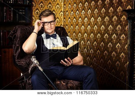 Handsome well-dressed man sitting in the armchair by bookshelves in a room with classic vintage interior. Fashion. Luxury.