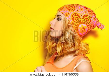 Portrait in profile of a pretty girl with curly blonde hair wearing bright clothes and posing over yellow background. Bright style, fashion.