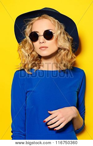 Pretty girl with curly blonde hair wearing bright clothes and sunglasses posing over yellow background. Bright style, fashion. Optics style.