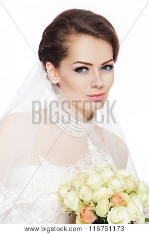 Young beautiful bride with stylish make-up and hairdo holding bouquet