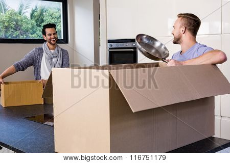Smiling gay couple unpacking cardboard in the kitchen