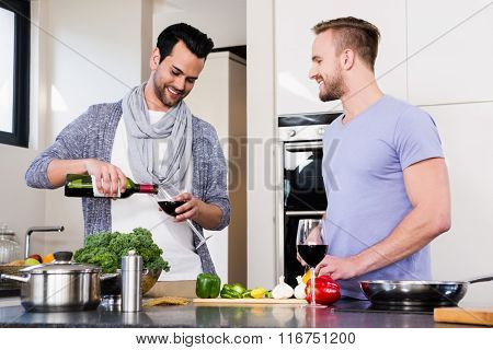 smiling gay couple preparing food in the kitchen
