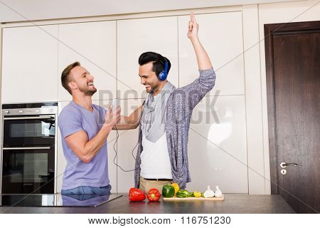 Smiling gay couple having fun while preparing food in the kitchen