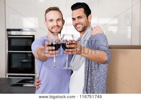 Smiling gay couple toasting with red wine while unpacking cardboard