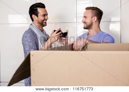 Smiling gay couple drinking red wine in the kitchen