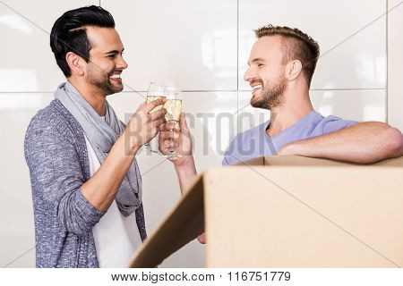 Smiling gay couple toasting with champagne while unpacking cardboard
