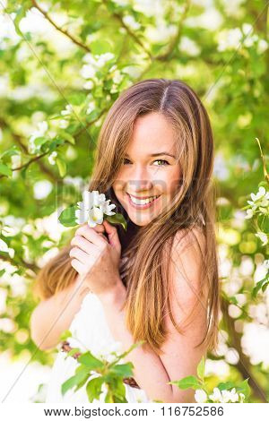 Beautiful happy young woman in the spring garden among apple blossom, soft focus