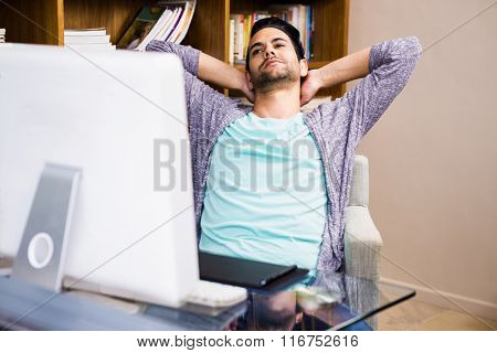 Handsome designer man relaxing at the desk in the office