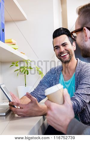 Happy gay couple using tablet at home
