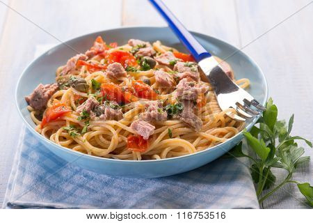 spaghetti with tuna capers and  tomatoes, selective focus