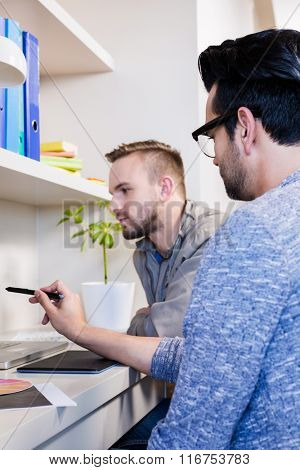 Serious gay couple using laptop in office